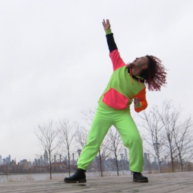 Zavé dances dressed in neon yellow and pinks reaching an arm up towards a white winter sky with their head tilted back looking up